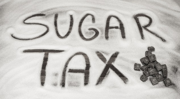 the words sugar tax written on a table in sugar