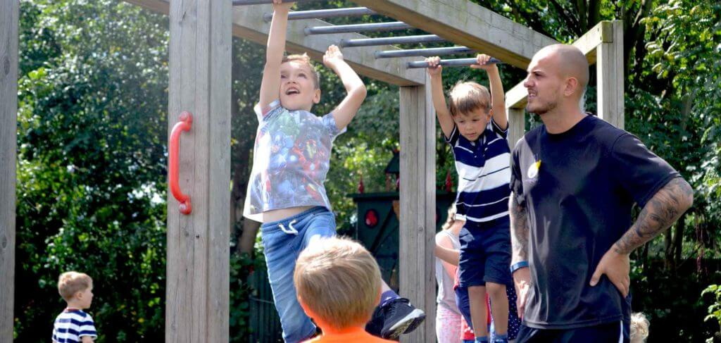 children playing on monkey bars while an adult keeps watch