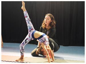 a child performing a dance position while a dancebugs teacher helps support them