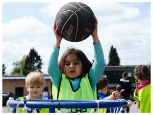 a child about to place a basket ball into a basket
