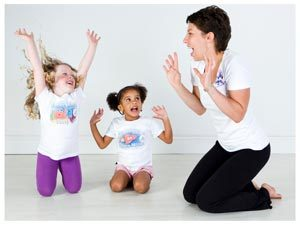 two young children and a yogabugs coach pretending to be lions