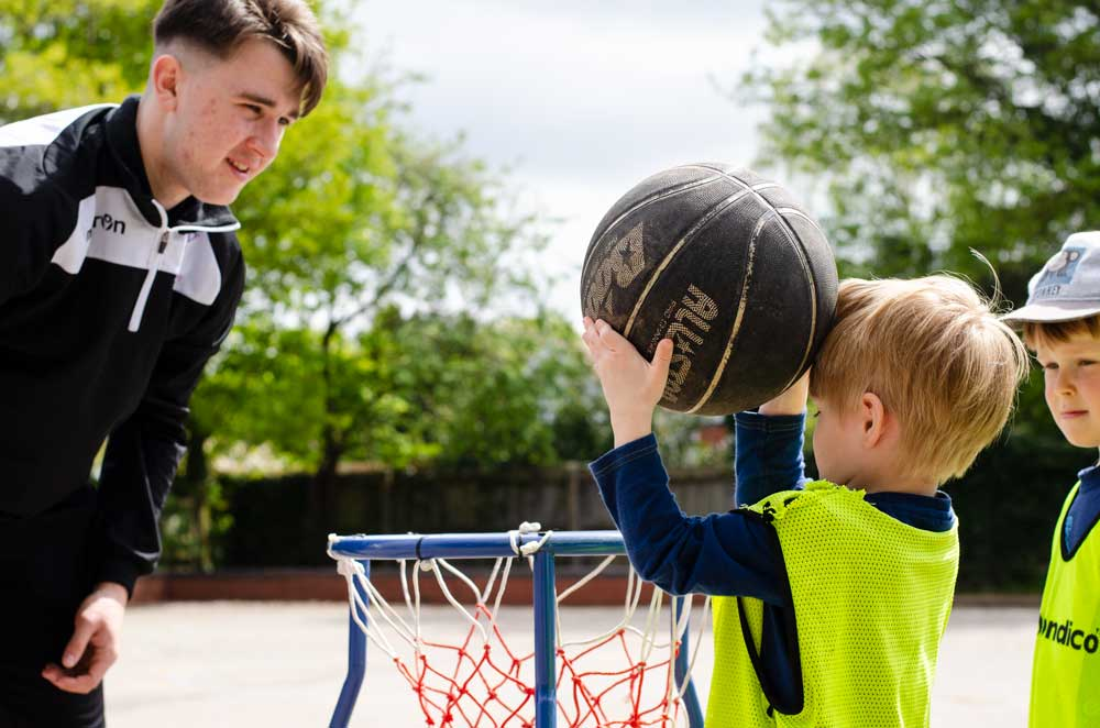 child putting a ball in a basketball hoop while a bugs group coach watches