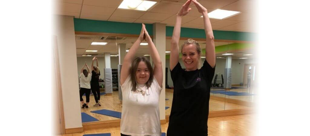 image of a yogabugs coach and an SEN child smiling and doing a yoga pose