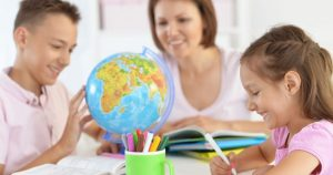 children studying a globe while a teachers watches them