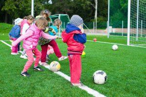 young children kicking footballs towards a goal outdoors
