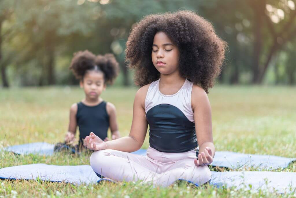 two young girls meditating in a field with their eyes closed