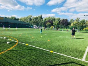 a football pitch at a sports centre with children playing on it and a footiegbugs coach leading the session