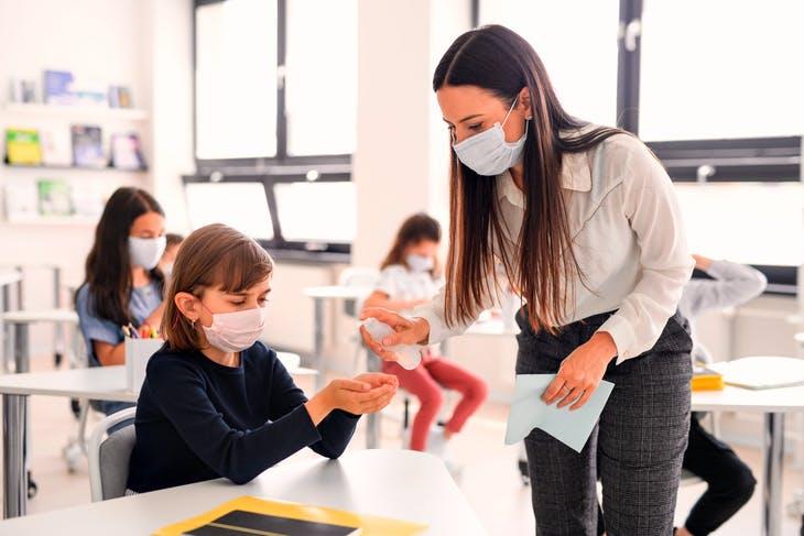 a teacher in a class helping a child sanitize their hands