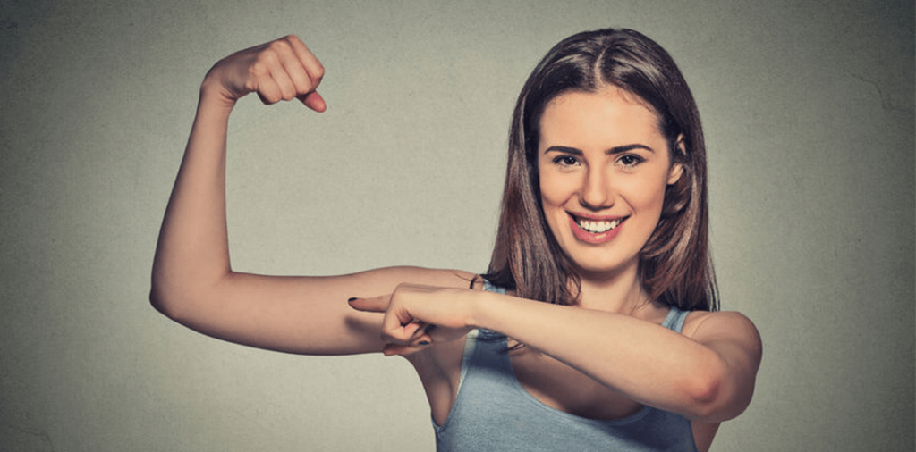 a girl making a muscle and pointing at it