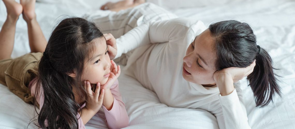 image of a mother and child on a bed talking